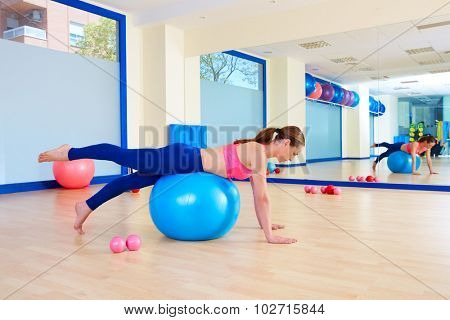 Pilates woman fitball leg pull front exercise workout at gym indoor