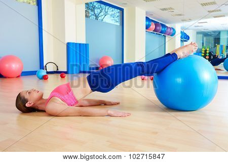 Pilates woman pelvic lift fitball exercise workout at gym indoor swiss ball