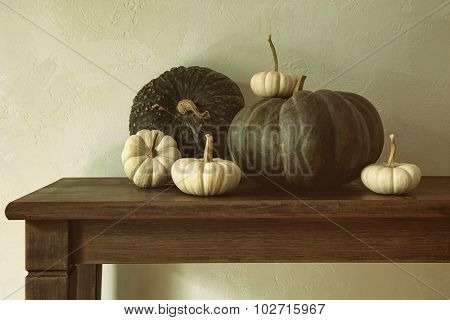 Green pumpkins and small gourds on wooden table