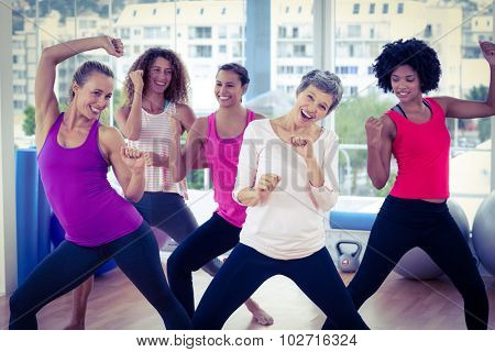Portrait of happy women exercising with clasped hands in fitness studio