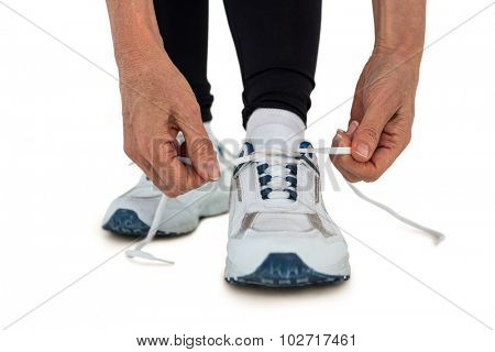 Low section of sporty woman tying shoelace against white background