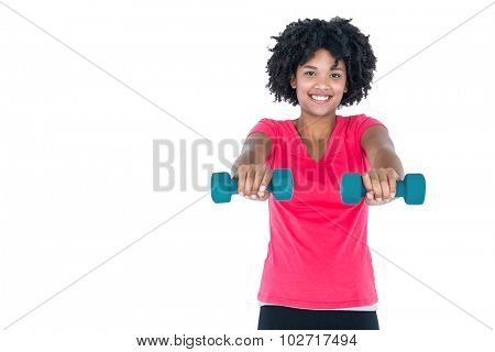 Portrait of happy young woman exercising with dumbbells against white background