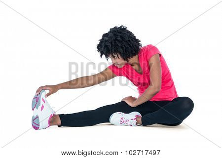 Fit young woman exercising against white background