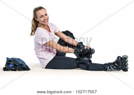 Portrait of cheerful sporty woman wearing inline skates over white background