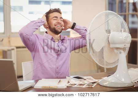 Relax businessman sitting at desk with electric fan in office