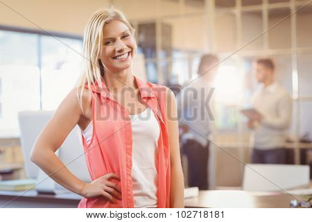 Portrait of smiling businesswoman with hand on hip standing against male colleagues working in creative office
