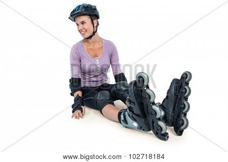Sporty woman wearing inline skates relaxing over white background