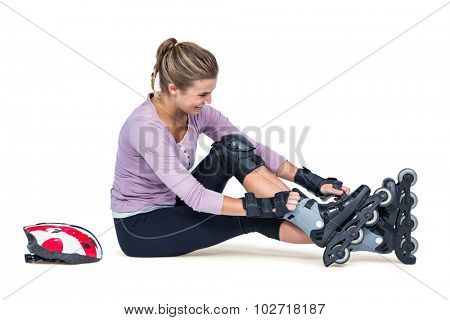 Young woman wearing inline skates while sitting over white background