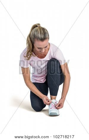 Sporty woman tying shoelace over white background
