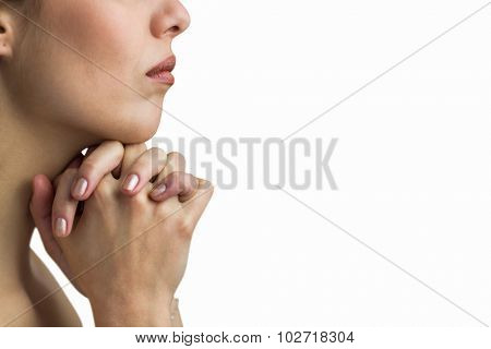 Close-up of woman praying with joining hands against white background