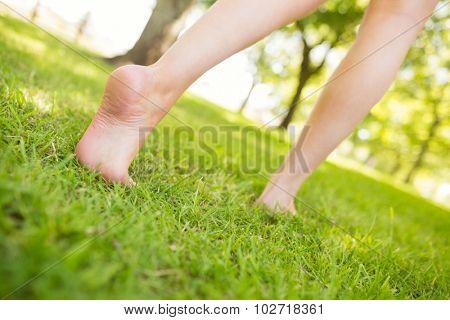 Low section tilt image of woman walking on grassland in park