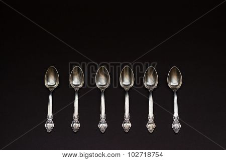 Six Silver Spoons In A Row On Black Background