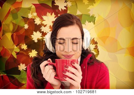 Woman in winter clothes enjoying a hot drink eyes closed against autumnal leaf pattern