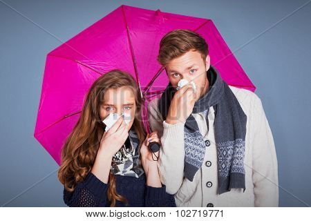 Couple blowing nose while holding umbrella against blue background
