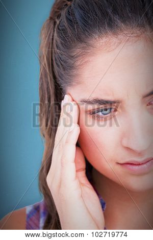 Close-up of beautiful woman suffering from headache against blue background