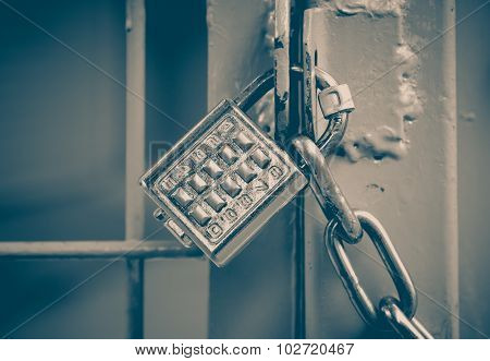 Metal padlock and pin keypad with numbers on metal door