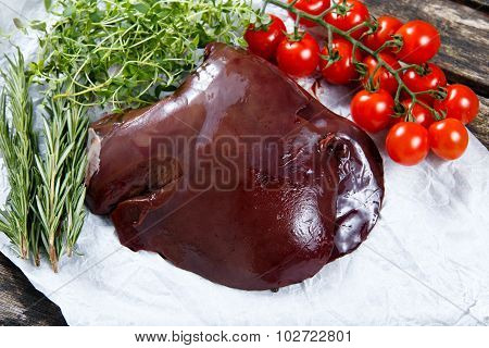 Raw Lamb Liver On Crumpled Paper,  Decorated With Greens And Vegetables. On Old  Wooden Table