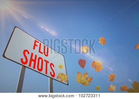 Autumn leaves pattern against low angle view of billboard against sky