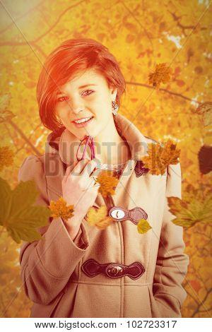 Portrait of pretty woman in winter coat holding glasses against autumn scene