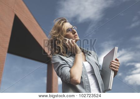 Young Businesswoman With Angry Or Upset Expression On Face Calling On Mobile Phone Holding Laptop In
