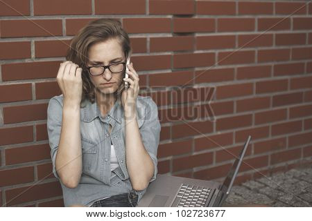 Upset Student Wornikg With Laptop, Thionking Of Something. Sitting Next To The Brick Wall.