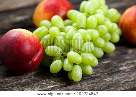 Green Grape And Nectarine Fruit Close Up, On Old Wooden Table. Background. Selected Focus