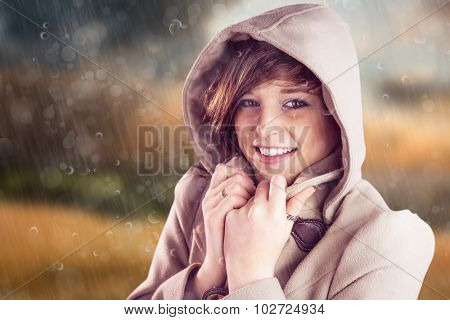 Portrait of smiling woman wearing winter coat against country scene