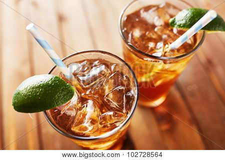 two cold glasses of iced tea with retro paper straw lime wedges on wooden table top. Shot with selective focus.