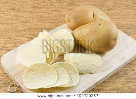 Potato And Potato Chips On Wooden Board