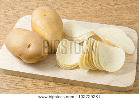 Potato And Potato Chips Or Crisp On Cutting Board