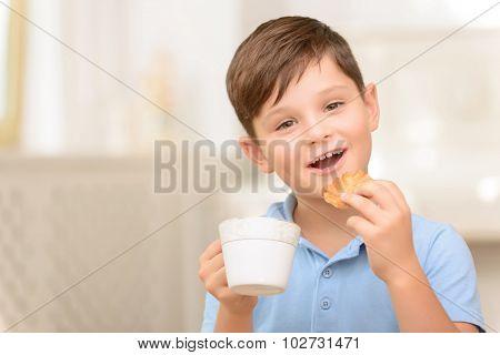 Joyful boy drinking tea