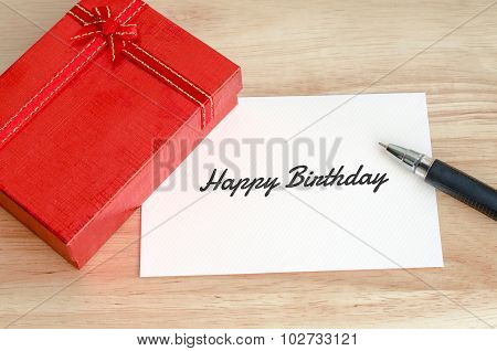 Red Gift Box With Blank Card And Pen On Wooden Table