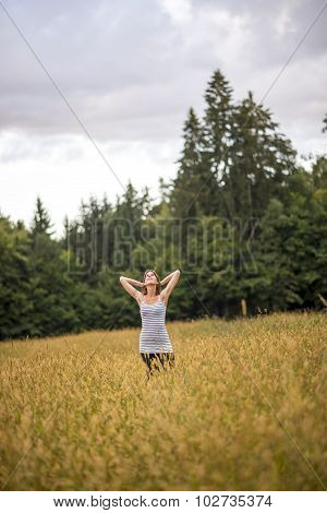 Young Woman Standing In An Autumn Field With High Grass