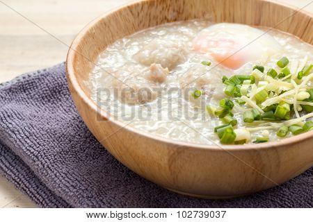Asian congee with minced pork and egg in white bowl.