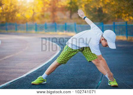 Boy Teen doing sports exercises on a stadium