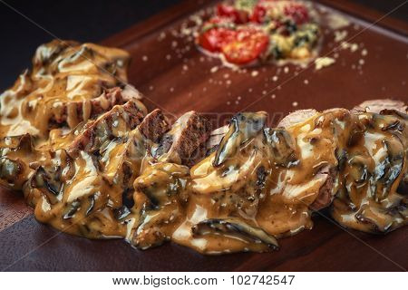 grilled beef with tomato in cream sauce on the board