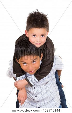 Two small hispanic boys playing, one carrying the other on his back, facing camera