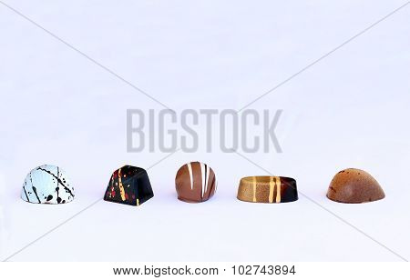 Five different chocolate bonbons in line