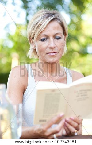 Cute woman reading a book outdoor and smilling