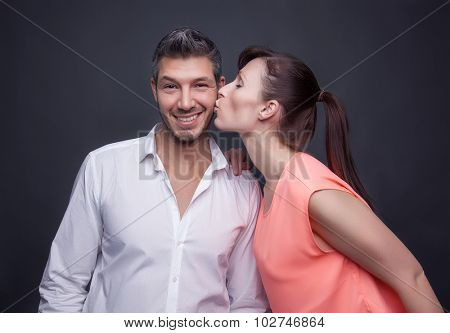 man enjoys getting kisses from girlfriend