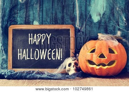 spiders, cobwebs, a skull, a jack-o-lantern and a chalkboard with the text happy halloween written in it