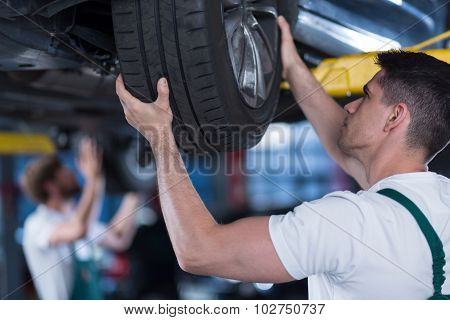 Car Mechanic Checking Wheel