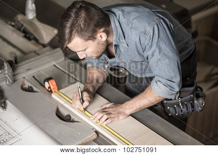 Carpenter Using A Measuring Tape