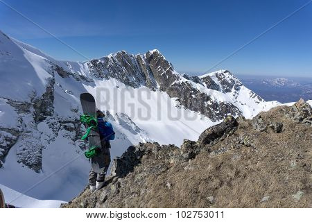 Snowboarder standing on top of a snowy mountain