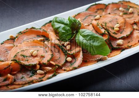 Salmon Carpaccio with nuts on white plate