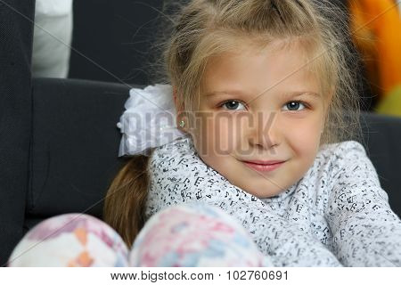 Thoughtful Blonde Little Girl Sitting On Floor