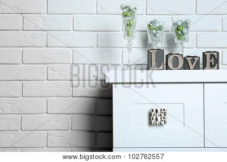 Decorative glasses with word Love on brick wall background