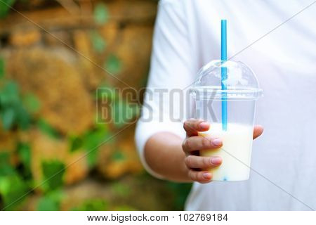 Woman holding plastic cup of milkshake  close-up, outdoors