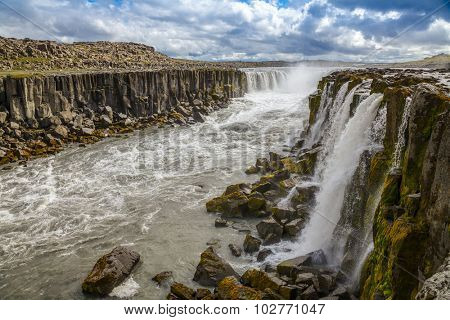 Selfoss is a horseshoe-shaped waterfall on the glacier river Jokulsa a Fjollum situated a few hundred meters upstream from the Dettifoss waterfall.