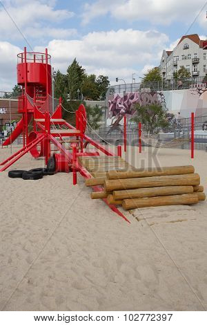kids playground with red slide climber and sandpit